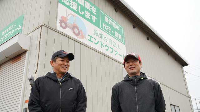 「地域農業を応援します」と格納庫の看板にも大きくアピール。目指す農業の夢を語り合う遠藤直道さん(左)と遠藤誠さん(右)